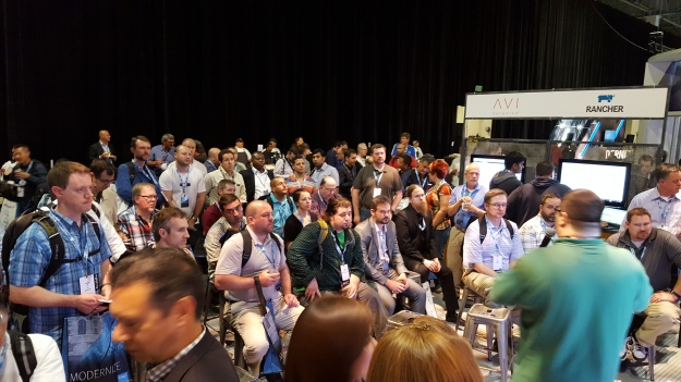 Mano Marks from Docker presenting at the booth in front of a large crowd